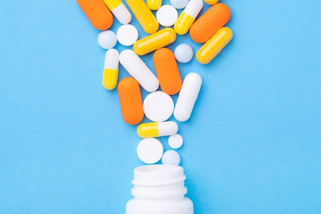 Multicolor tabletten en pillen capsules uit plastic fles op blauwe tafel close-up - afbeelding