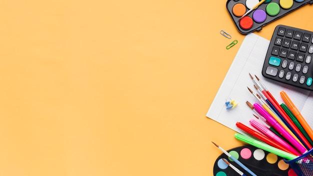Multicolored kantoorbehoeften en calculator op beige achtergrond