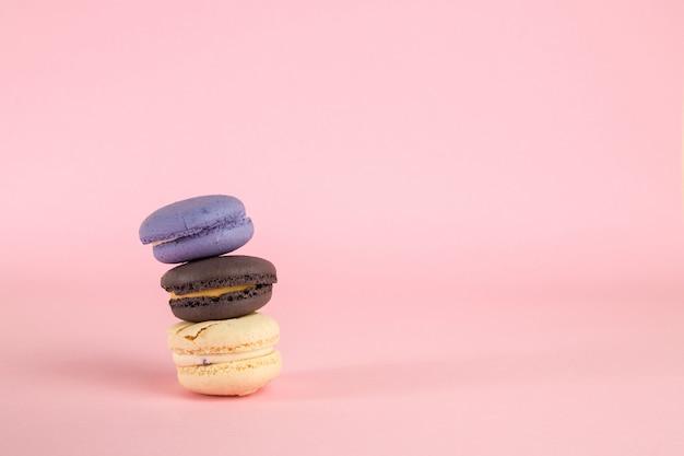 Multicolored macaronikoekjes op roze geïsoleerde achtergrond