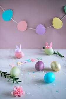 Multicolored paasei, roze, groen, blauw, goud met konijntjesoren op marmeren achtergrond