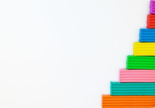 Multicolored plasticine op een witte achtergrond wordt gevestigd die. kinderen speelgoed achtergrond. frame met plaats voor tekst.