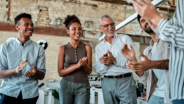 Multicultureel team klapt in de handen en glimlacht terwijl ze in het creatieve kantoor staan