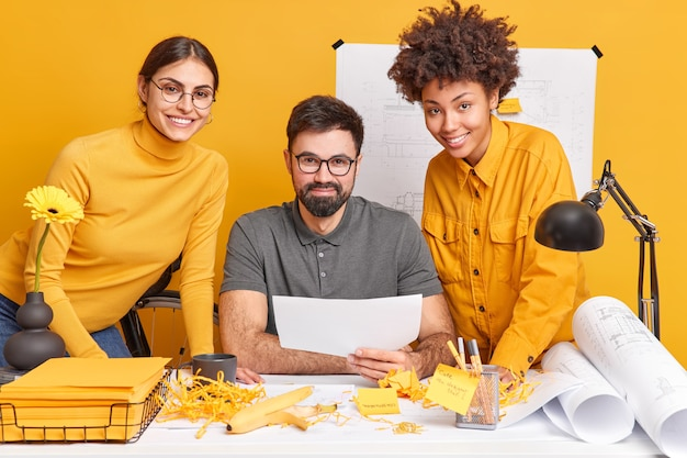 Multiculturele collega's werken samen aan een ontwerpproject bespreken ideeën voor illustraties samen poseren op een rommelig bureaublad teken blauwdrukken hebben gelukkige uitdrukkingen brengen overdag door in de werkruimte ontwerp ontwikkelen