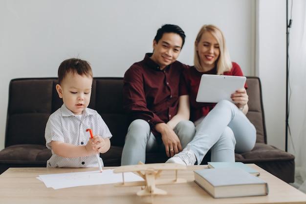 Multiculturele gelukkige familie. aziatische man en blanke vrouw met hun zoon kijken naar video op tablet en telefoon.