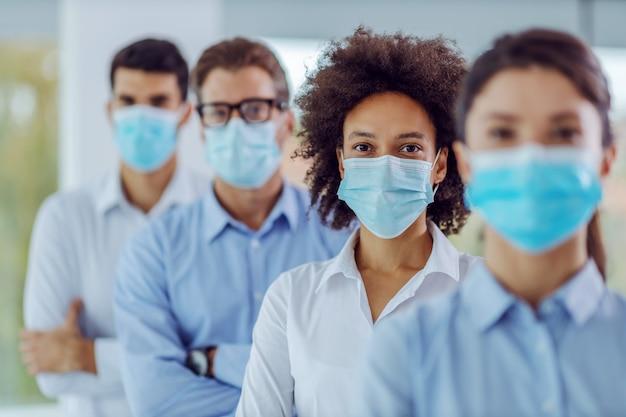 Multiculturele groep bedrijfsmensen met gezichtsmaskers bij status in bureau met gekruiste wapens. selectieve focus op vrouw van gemengd ras in het midden.