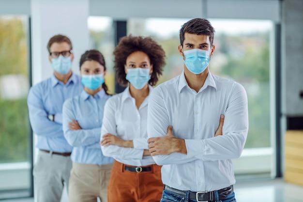 Multiculturele groep bedrijfsmensen met gezichtsmaskers op status in bureau met gekruiste wapens en camera kijken