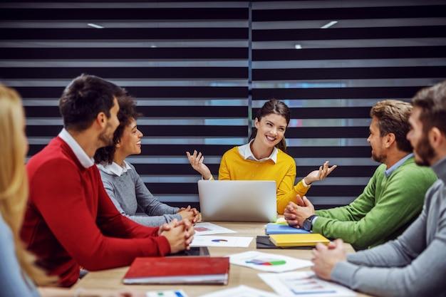 Multiculturele groep van positieve bedrijfsmensen die in directiekamer zitten over vergadering.
