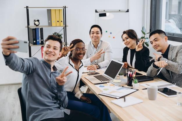Multiculturele groep van professionele zakenmensen selfie maken in een modern kantoor