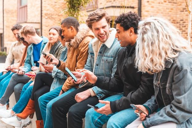 Multiculturele groep vrienden gebruikend smartphone en hebbend pret