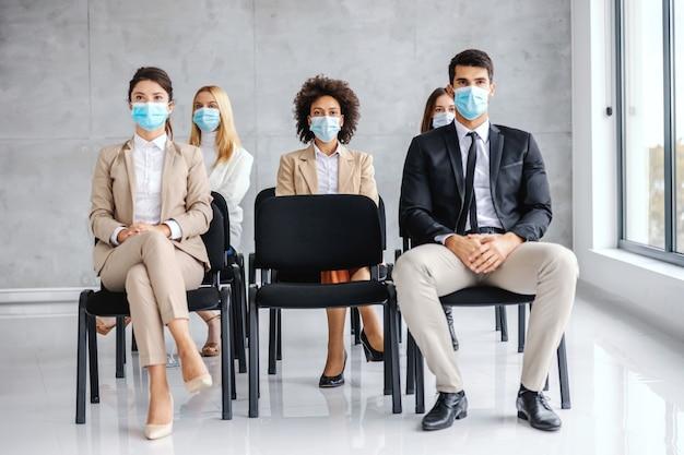 Multiculturele groep zakenmensen met gezichtsmaskers zittend op seminar tijdens coronavirus.