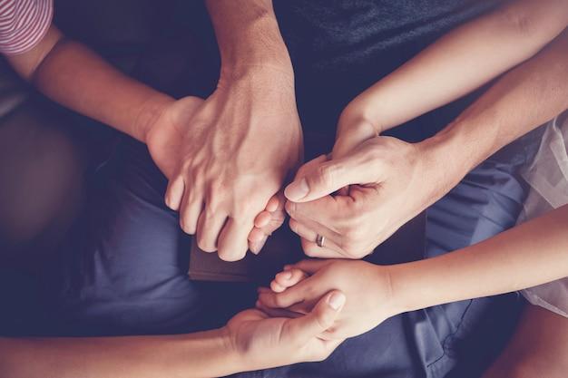 Multiculturele kinderen bidden thuis met hun vader