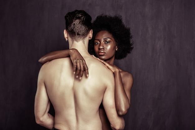 Multiculturele liefhebbers. ernstige afro-amerikaanse vrouw die naar je kijkt terwijl ze achter haar vriendje staat