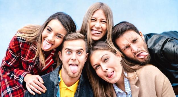 Multiculturele milenial jongens en meisjes die selfie nemen en tong uitsteken met blije gezichten