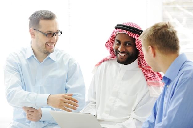 Multiculturele verschillende etnische groep die aan laptop samen werkt