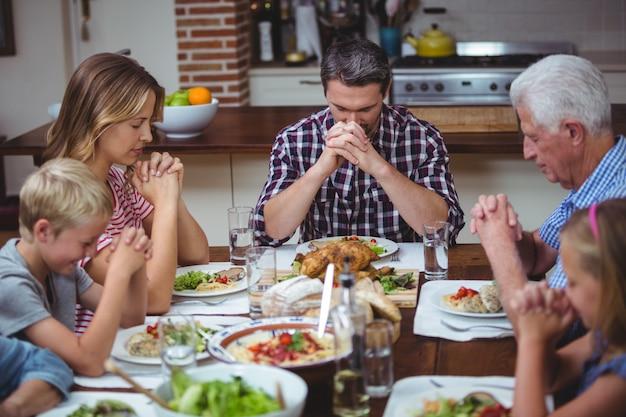Multigeneratiefamilie die met grootouders bidden die bij eettafel zitten