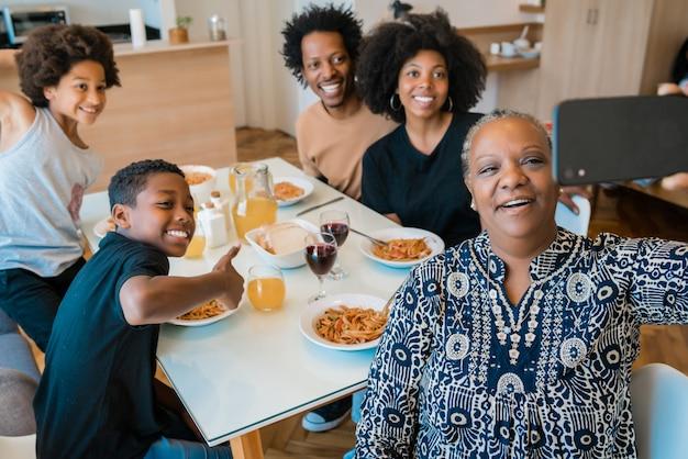 Multigenerationele familie die selfie met telefoon thuis nemen.