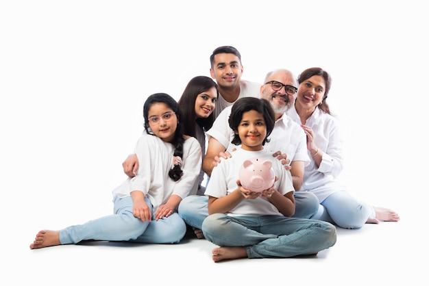 Multigenerationele indiase familie van zes die een spaarvarken vasthoudt terwijl ze witte doeken draagt en tegen een witte muur staat