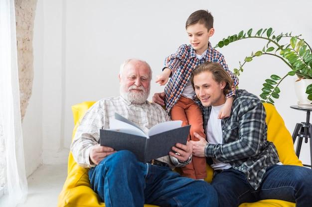 Multigenerationele mannen die naar een album kijken