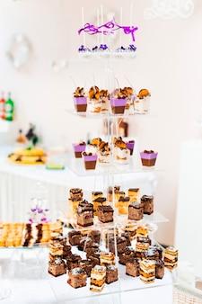Multilevel transparante standaard met stukjes cake en cupcake.