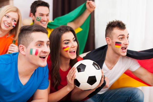 Multinationale vrienden juichen voetbalwedstrijd thuis