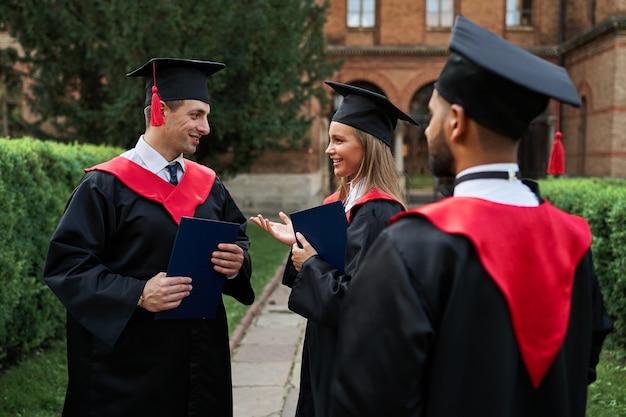 Multinationale vrouwelijke en mannelijke afgestudeerden spreken in afstudeergewaden op de universiteitscampus.
