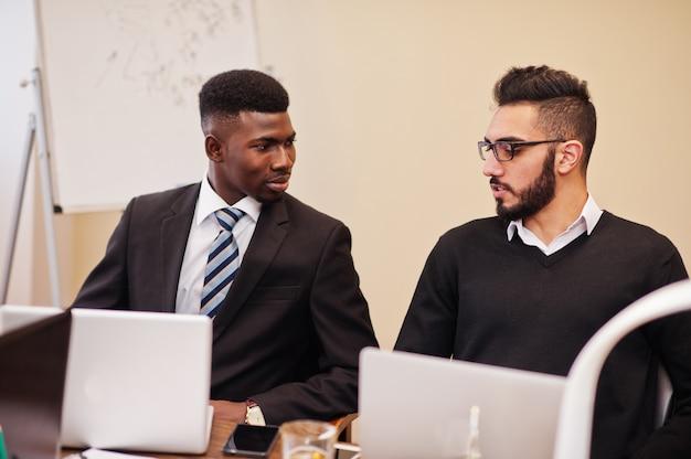 Multiraciaal commercieel team dat vergadering rond bestuurskamerlijst richt. afrikaanse en arabische zakenman.
