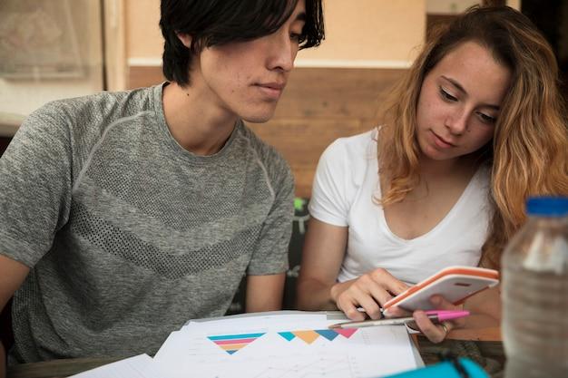 Multiraciaal jong paar dat in calculator dichtbij diagrammen op papier kijkt