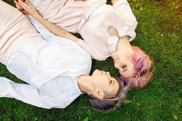 Multiraciaal lesbisch paar die op het gras liggen.