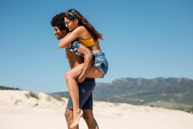Multiraciaal paar dat op strand loopt
