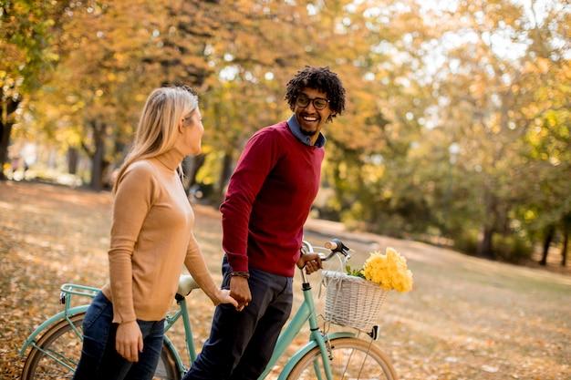 Multiraciaal paar met fiets die zich in het de herfstpark bevindt