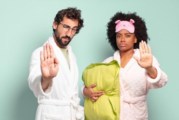 Multiraciaal paar vrienden die ernstig, streng, ontevreden en boos kijken en open palm tonen die stopgebaar maken. pyjama's en huisconcept