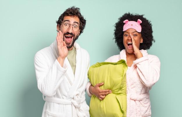 Multiraciaal paar vrienden die zich gelukkig, opgewonden en positief voelen, een grote schreeuw geven met hun handen naast de mond, roepen. pyjama's en huisconcept