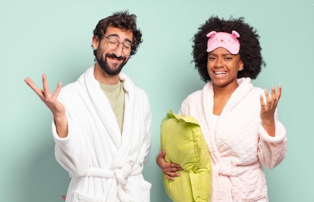 Multiraciaal paar vrienden die zich gelukkig, verrast en opgewekt voelen, glimlachend met een positieve houding, een oplossing of idee realiserend. pyjama en woonconcept
