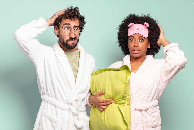 Multiraciaal paar vrienden die zich gestrest, bezorgd, angstig of bang voelen, met de handen op het hoofd, in paniek raken bij een fout