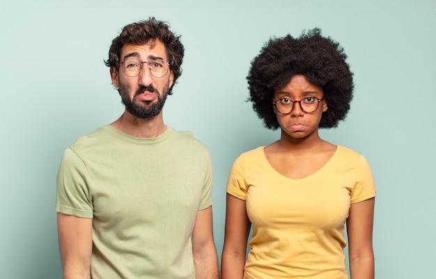 Multiraciaal paar vrienden die zich verdrietig en zeurderig voelen met een ongelukkige blik, huilen met een negatieve en gefrustreerde houding