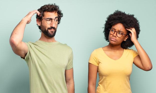 Multiraciaal paar vrienden die zich verward en verward voelen, hoofd krabben en opzij kijken