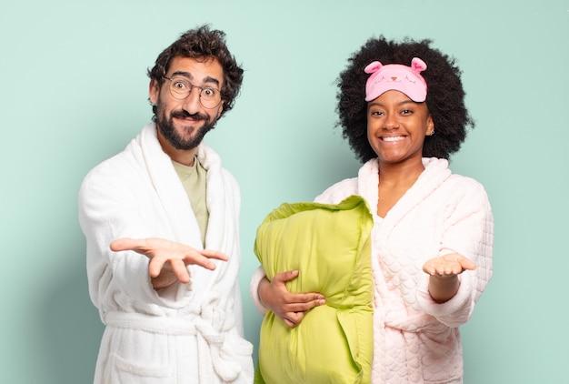 Multiraciaal paar vrienden glimlachend gelukkig met vriendelijke, zelfverzekerde, positieve blik, aanbieden en tonen van een object of concept. pyjama's en huisconcept