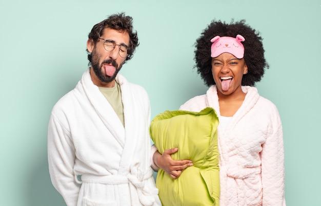 Multiraciaal paar vrienden met een vrolijke, zorgeloze, rebelse houding, grappen maken en tong uitsteken, lol hebben. pyjama's en huisconcept