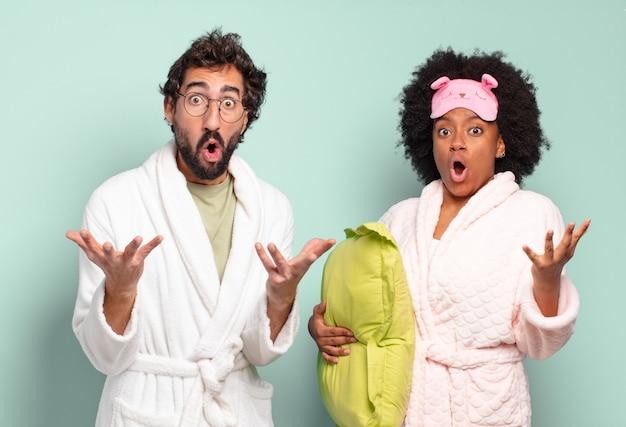Multiraciaal paar vrienden met open mond en verbaasd, geschokt en verbaasd over een ongelooflijke verrassing