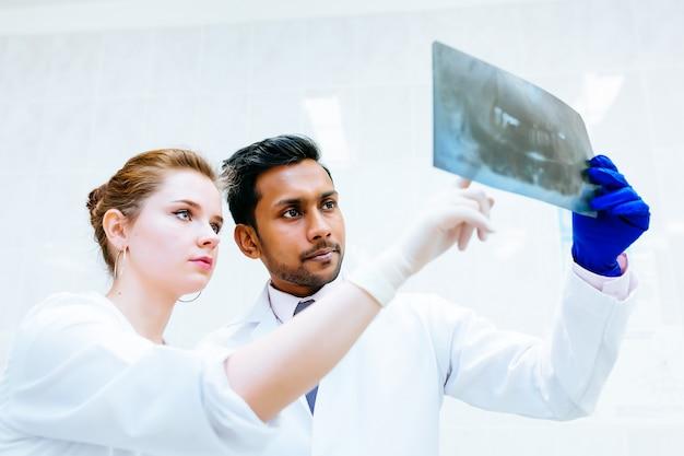 Multiraciaal tandteam dat tandenröntgenstraal van patiënt controleert. tandheelkundige kliniek concept.