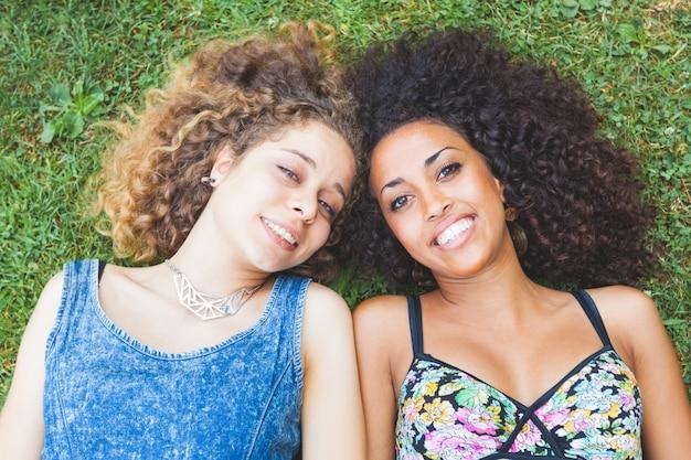 Multiraciaal vrouwelijk paar vrienden die op het gras liggen