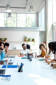 Multiraciale collega's bespreken bedrijfsstrategieën met indiase mannelijke baas ruimte kopiëren verticale afbeelding