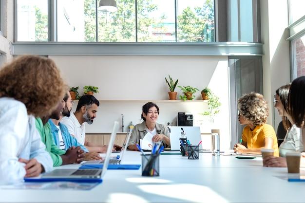 Multiraciale collega's delen ideeën tijdens zakelijke bijeenkomsten in een licht, ruim kantoor ruimte kopiëren