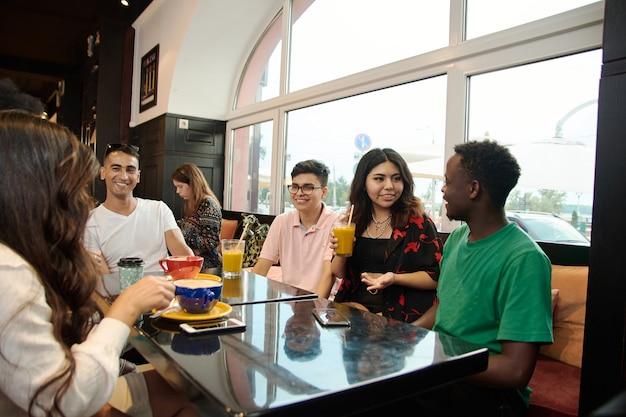 Multiraciale gelukkige jonge mensen drinken koffie in café, zwarte en witte vrolijke vrienden lachen genieten van drankjes met plezier samen zitten aan de tafel van het restaurant, diverse vrienden delen lunch tijdens de vergadering.