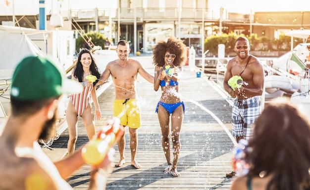 Multiraciale gelukkige vrienden die gekke pret met watergevechtsstrijd hebben bij de zomerplaats