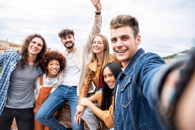 Multiraciale gelukkige vrienden vieren samen het nemen van selfie portret op straat in de stad - jongeren die plezier hebben samen lachen in de buitenlucht - gelukkige levensstijl en vriendschap concept