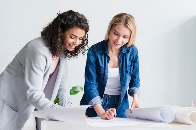 Multiraciale glimlachende werknemers die met documenten werken