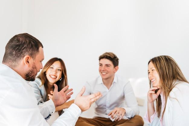 Multiraciale groep collega's die aan spreker luisteren