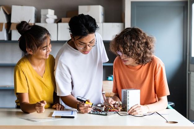 Multiraciale groep middelbare scholieren leren samen elektronica onderwijssamenwerking