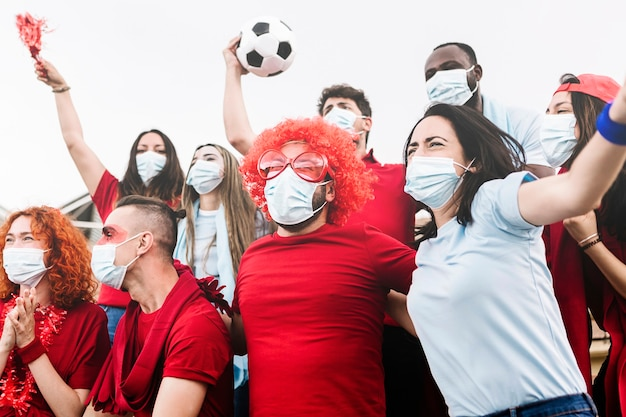 Multiraciale groep sportfans in beschermend gezichtsmasker schreeuwend in het stadion